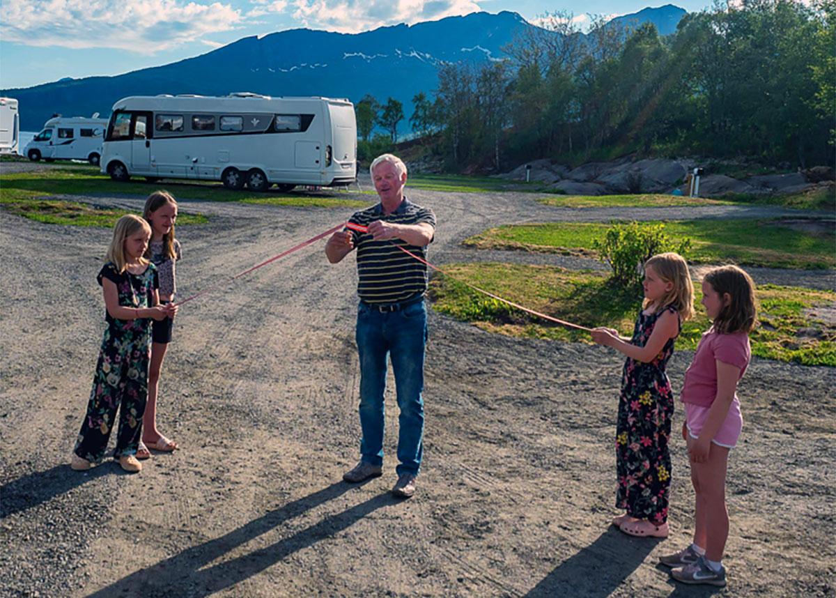 Mann klipper snor , barn og bobiler i bakgrunn overnatting i Hamarøy